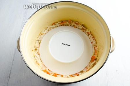 Сверху капусту накрыть тарелкой. Придавить грузом. Накрыть марлей. Поставить кастрюлю в тёплую комнату.