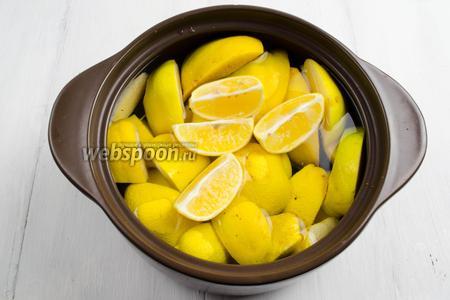 Лимон вымыть. Нарезать тоже на 4 доли. Добавить в кастрюлю к айве. Поставить кастрюлю на огонь. Довести до кипения. Уменьшить огонь и варить айву в течение 30 минут. Воду слить. Дольки лимона выбросить.