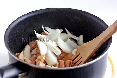 К слегка обжаренной курице добавить лук и чеснок. Жарить, при постоянном помешивании, на среднем огне минуты 2.