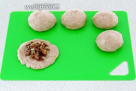 Из полученной массы сформовать лепёшки (по 4 штуки на порцию), на середину их разложить начинку и завернуть каждую лепёшку в форме шарика (клёцки). Шарики слегка приплюснуть.