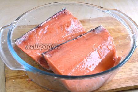 Выложите куски рыбы в стеклянную или керамическую ёмкость и полейте коньяком. Пока вы подготавливаете специи, пусть рыба немного пропитается алкоголем.