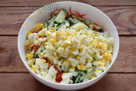 Очистите куриные яйца и нарежьте кубиком. Измельчённые яйца добавьте в салатник.