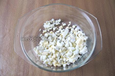 Яйца сварить вкрутую, охладить и почистить. После нарезать кубиком и выложить в миску.
