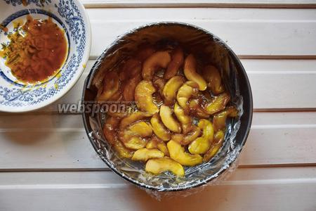 Выложить остывшие яблоки на дно формы, проложенной пищевой плёнкой.