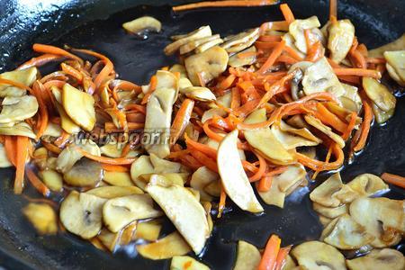 Заливаем морковь с грибами заправкой и сразу мешаем. Обжариваем, помешивая около 1 минуты. К этому времени гречневая лапша уже должна быть отварена.