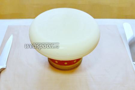 В микроволновке нагреваем глазурь (не перегрейте, будет долго остывать), снимаем плёнку и пробиваем ещё раз блендером, измеряем температуру, должна быть 30-35°С. Если образовались пузырьки, нужно снова процедить через сито в кувшин с носиком (из такого заливать удобнее). Глазурь готова и только теперь вынимаем заготовку торта из морозилки (иначе образуется конденсат на поверхности торта и подпортит нам глазурь), освобождаем от формы и устанавливаем на подставку.