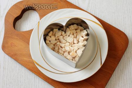 На тарелку ставим форму. Укладываем салат слоями: 1 слой — куриное филе, мелко порезанное, смазываем майонезом или делаем майонезную сеточку.