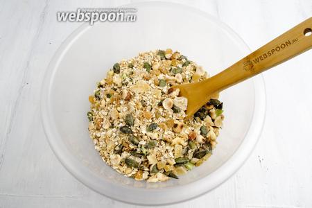Орехи измельчить. Высыпать в глубокую посуду. Добавить цукаты, кокосовую стружку, подготовленный изюм, овсяные хлопья и соль. Всю массу перемешать.