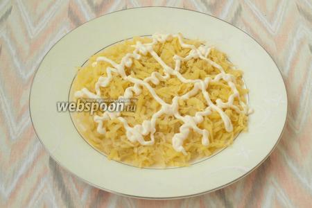 Отварной картофель очистить и натереть на тёрке. Выложить на блюдо и нанести майонезную сетку.