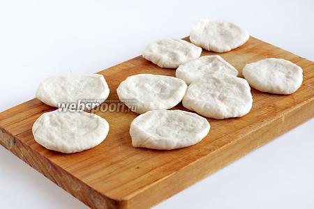 Для удобства в работе разделить тесто на 2 части. 1  часть оставить под полотенцем, работать со второй. Сформировать колбаску и нарезать её на равные кусочки, чуть побольше, чем для вареников. Приплющить каждый кусочек в лепёшку.