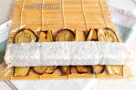 На край циновки выложить печёные слайсы баклажана стык в стык, один к другому. Сверху положить на них наш рулон.