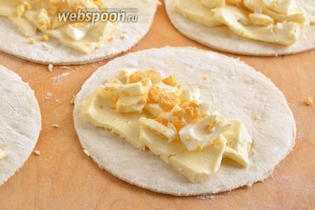Раскатайте тесто толщиной примерно в 0,4 см и вырежьте из него кружочки, размером с десертную тарелку (около 12-13 см). Сверху выложите ломтики сыра и яиц. Иногда в начинку добавляют маленькие кусочки сливочного масла для сочности, но я обошлась без него.