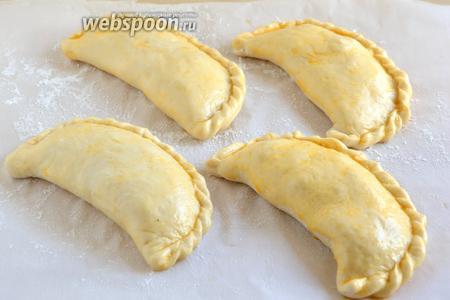 Смажьте пирожки желтком и дайте ещё раз подойти в тёплом месте. В это время разогрейте духовку до 220°С.