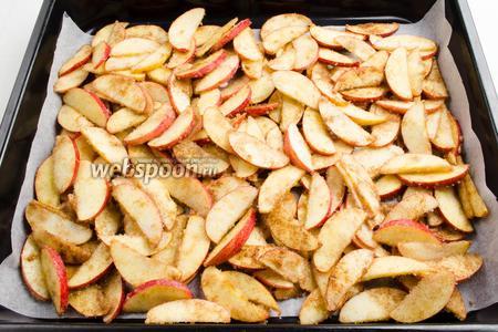 Выложить яблочные дольки на противень. Поставить противень в горячую духовку. Оставить его на 25 минут при температуре 200°С.