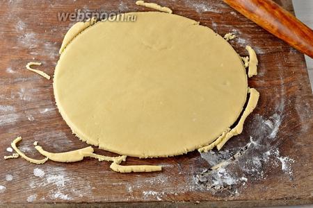 Каждую часть раскатать на слегка подпылённой мукой доске и вырезать круг диаметром 24 сантиметра.