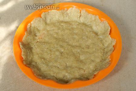 Достаём из холодильника тесто и утрамбовываем его по форме, формируя бортики.