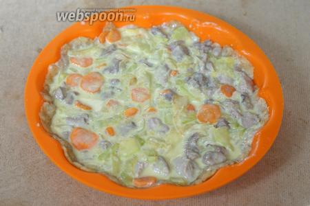 Соединяем 1 яйцо, сметану (50 г), индейку и овощи, солим и перчим по вкусу и выкладываем начинку на основу.