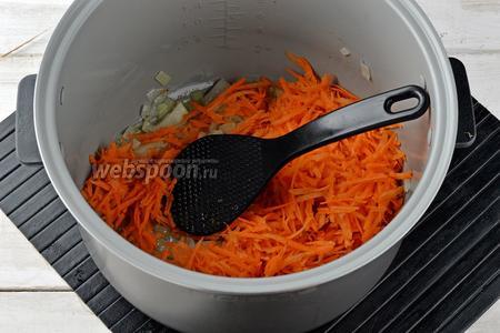 Добавить очищенную и натёртую на крупной тёрке 1 морковь. Перемешать и жарить 3 минуты.