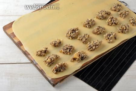 На половину теста порциями (по 1 чайной ложке) выложить начинку, соблюдая расстояние между порциями начинки 3-3,5 сантиметра.