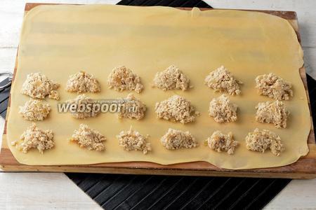 Тесто (берите на 1 раскатку 1/3 часть теста) раскатать на присыпанной мукой рабочей поверхности до полупрозрачного состояния. На половину теста выложить порциями начинку, соблюдая расстояние между порциями начинки, приблизительно 3 сантиметра.