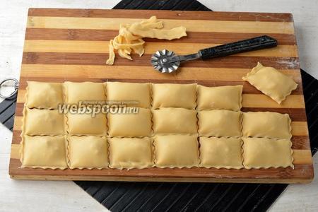 С помощью специального колесика (или ножом) разрезать тесто на равиоли. Проверьте, плотно ли соединено тесто по краям  у каждой равиоли.