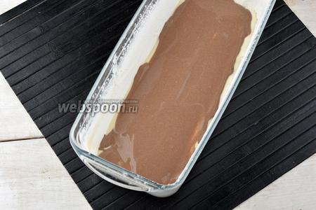Форму для выпечки смазать сливочным маслом (1 ст. л.). Присыпать пшеничной мукой (1 ст. л.). Выложить часть белого теста на дно. Сверху равномерно распределить часть шоколадного теста.