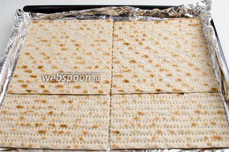 На противень расстелить фольгу или пергамент. Смазать поверхность тёплым сливочным маслом (20 г), чтобы карамель не прилипла. Разложить мацу (4 шт.) по всей поверхности.