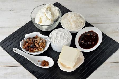 Для работы нам понадобится пастообразный жирный творог (если творог с крупинками, то пропустите его через сито), сахар, мука, грецкие орехи, изюм, любое варенье (у меня варенье из кусочков слив с грецкими орехами и изюмом), корица, молоко, сливочное масло.
