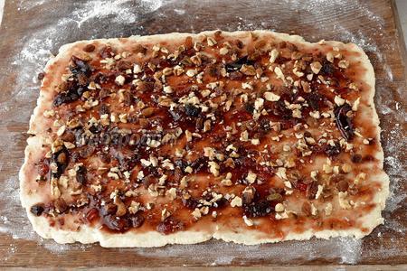 Смазать тесто вареньем (5 ст. л.), посыпать нарезанными грецкими орехами (0,25 стакана) и изюмом (5 ст. л.).
