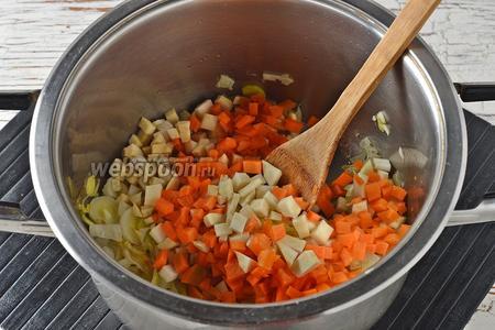 Морковь (70 г) и корень сельдерея (100 г) очистить и нарезать маленькими кубиками. Добавить овощи в кастрюлю и томить, помешивая, 5-7 минут.