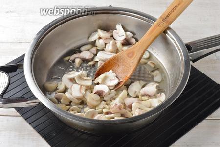 На другой сковороде с подсолнечным маслом (1 ст. л.), параллельно, обжарить очищенные и нарезанные небольшими кусочками шампиньоны (250 г) до готовности. В конце добавить очищенный и мелко нарезанный чеснок (1 зубчик), перемешать и готовить ещё 1 минуту.