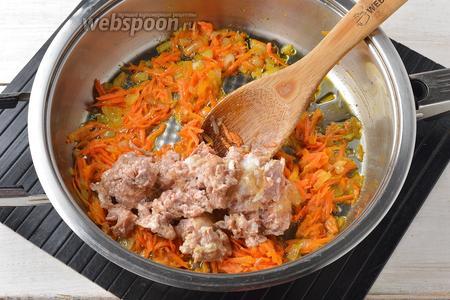 Добавить очищенную и натёртую на тёрке с крупными отверстиями 1 морковь. Готовить, помешивая, до мягкости моркови. Добавить тушёнку (300 г), перемешать и готовить минут 5, до выкипания жидкости.