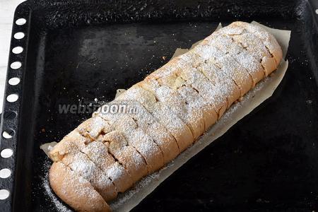 Вынуть противень. Горячий штрудель сразу же нарезать на порционные кусочки, так как потом, после охлаждения, при нарезке штрудель будет крошиться. Присыпать штрудель сверху сахарной пудрой.
