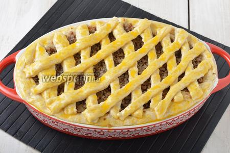 Меньшую часть теста раскатать. Нарезать из теста полоски и выложить их на начинку. Смазать пирог сверху 1 желтком.