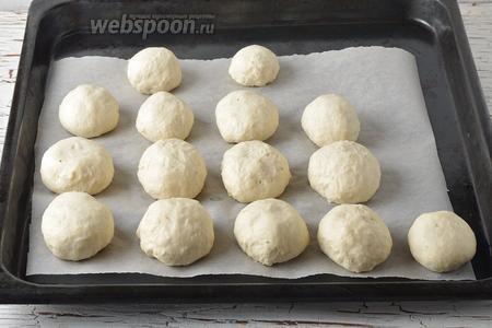 Противень выложить кулинарной бумагой. Сформировать из теста небольшие булочки и выложить их на бумагу, соблюдая между ними расстояние. Оставить булочки в тёплом месте на 15-20 минут.