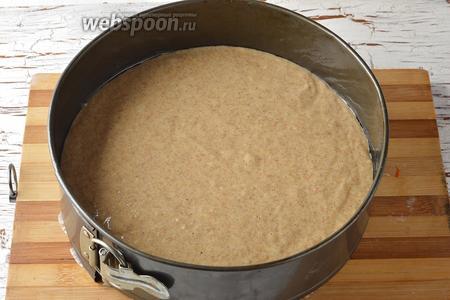 Форму (диаметром 24 сантиметра) выложить кулинарной бумагой. Выложить тесто в форму и разровнять.