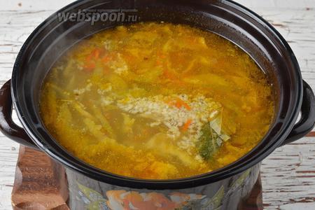 Выложить в кастрюлю подготовленные лук и морковь, фасоль без отвара, 1 лавровый лист. Довести до кипения и готовить на небольшом огне 5 минут. Проверить ещё раз на соль. Снять с огня, выложить в кастрюлю очищенный и пропущенный через пресс чеснок (3 зубчика). Закрыть крышкой и оставить на 5 минут.