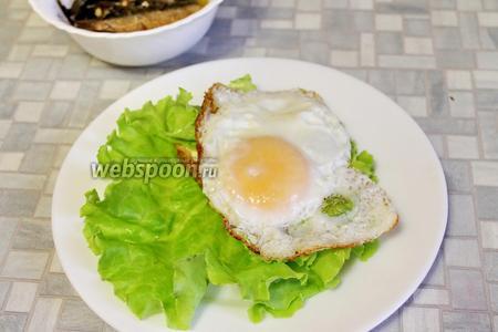 Положить хлеб на салатный лист, второй лист (или часть большого листа) положить на майонез, а сверху — глазунью.