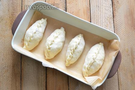 Такие же пирожки можно и выпекать в духовке: для этого прижимать их не нужно. Выкладываем пирожки в керамическую форму и оставляем для подхода на 10-15 минут. Затем смазываем верх взбитым яйцом и отправляем в духовку.