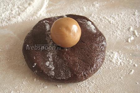 Шарик руками преобразуем в лепёшку и кладём посередине конфетку (первой у меня в ход пошла карамель с шоколадно-ореховой начинкой).