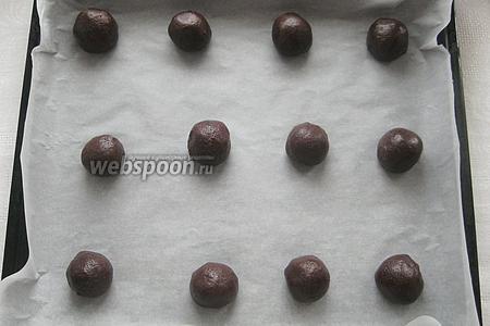 Подвернув края теста, снова формируем из него шарик, оставляя карамель внутри. Повторяем эту «операцию» с половиной шоколадных шариков, поочередно выкладывая их на противень, выстланный бумагой для выпечки.
