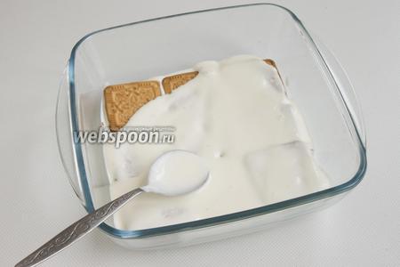 В форму с высокими краями выложите слоями сметанный крем и печенье. Начинать нужно с небольшого количества крема.