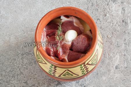 Укладываем мясо поверх картошки, слегка солим, перчим, укладываем поверх мяса чищенный зубчик чеснока и веточку тимьяна.