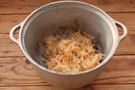 Квашеную капусту отожмите от рассола.  На дно казана влейте растительное масло (2-3 столовые ложки) разогрейте. Теперь в казан кладём капусту и начинаем тушить её. Помешивайте время от времени. Время тушения капусты около 20 минут.