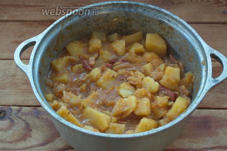 Когда картофель будет почти готов, добавьте в казан соль, специи по вкусу. Если томатная паста или капуста слишком кислые, добавьте немного сахара. Тушите до готовности блюда. За минуту до выключения огня выдавите в казан чеснок. Перемешайте. Блюдо готово.