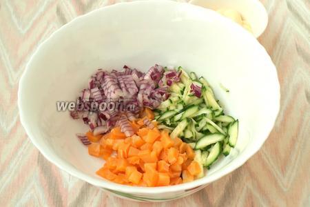 Небольшими кубиками нарезать фиолетовый лук, добавить к огурцам и кальмару.