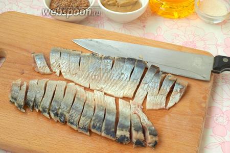 Острым ножом нарезать селёдку тонкими ломтиками.