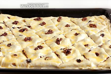 В центр каждого ромбика поместить по 1 орешку. Выпекать пахлаву в разогретой до 180°С духовке, пока она не станет румяной. Время выпечки может быть разным, примерно — 25 минут.