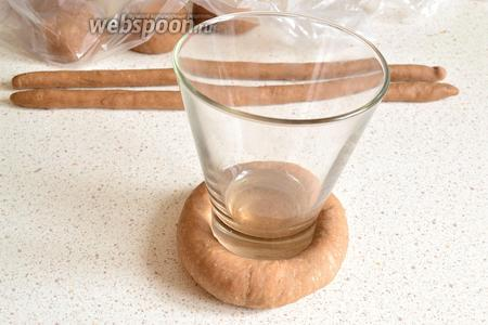 Сначала делаем сметанники в форме обычной ватрушки. Для этого круглую заготовку немного прижмём. Затем опускаем донышко стакана в муку, ставим стакан на заготовку и нажимаем на стакан. Получаем заготовку для ватрушки с выемкой и бортиками. Стакан убираем.