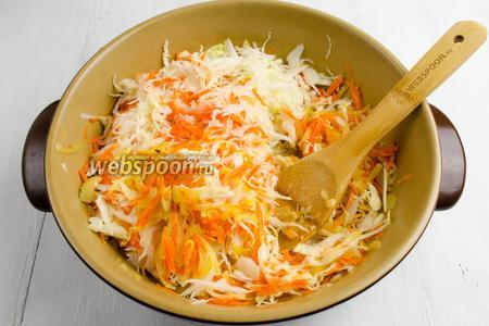 Добавить капусту с морковью частями на сковороду, размешивая, продолжить тушение на среднем огне.